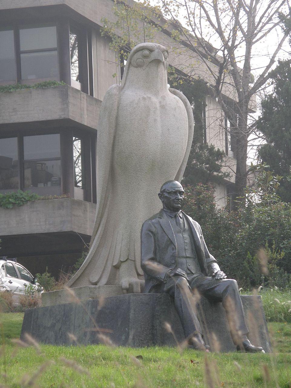 Photograph of statue of Gulbenkian, overseen by Horus, in the garden, Lisbon.