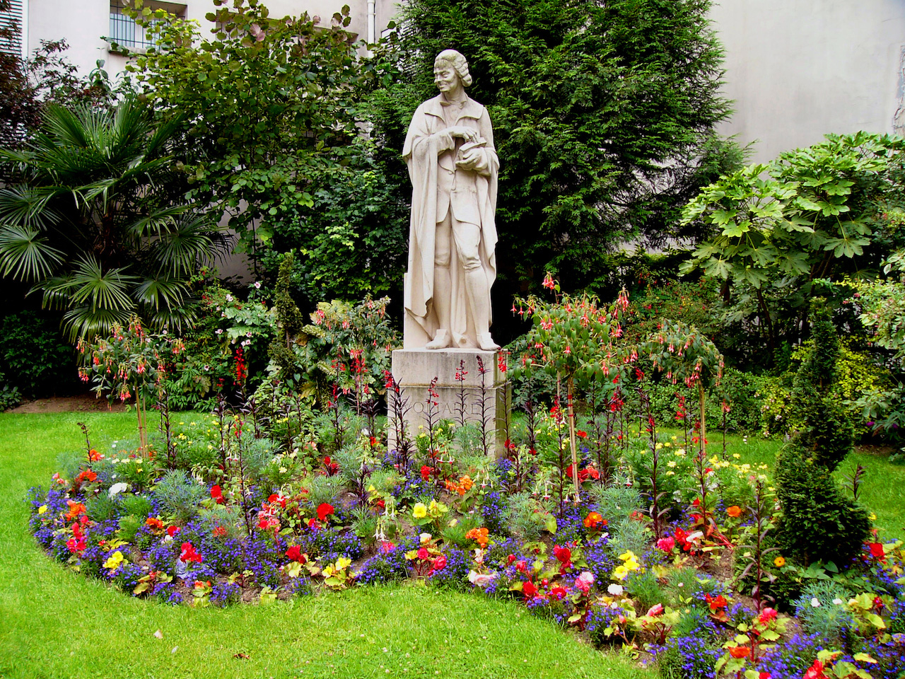 Statue of Voltaire placed in the middle of a bed of flowers in bloom.